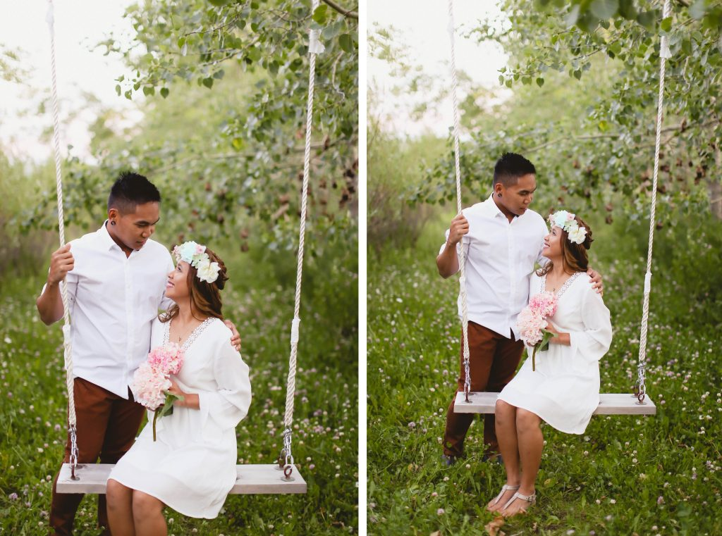 Cute couple on a swing photography. Girl is wearing a white dress and holding pretty pink flowers.