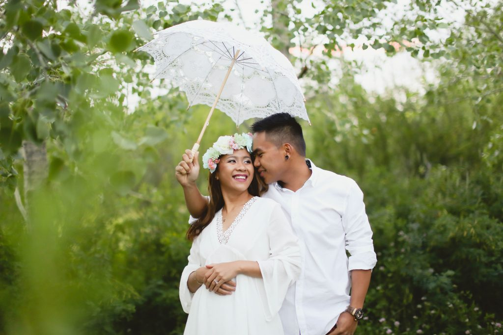 Couple under a white umbrella at farm house vintage rentals located near grande prairie. They have such beautiful smile and emotion.Couple under a white umbrella at farm house vintage rentals located near grande prairie. They have such beautiful smile and emotion.