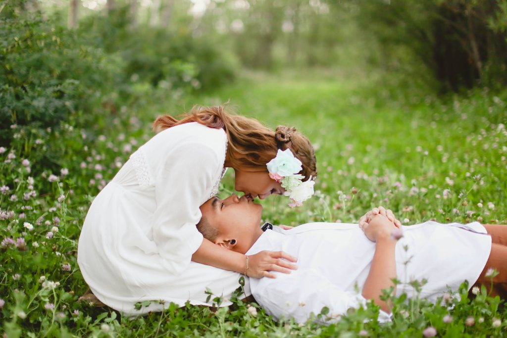 Girl giving her husband a kiss in the beautiful green grass. The girl is wearing a beautiful white dress and flower crown.