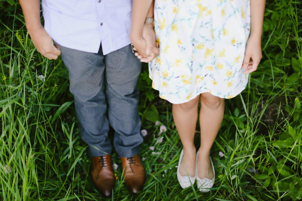 Couple holding hands. They are wearing fancy shoes, beautiful patterned dress and pants.