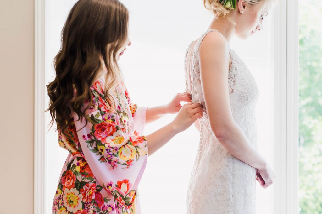 maid of honor tying wedding dress for bride