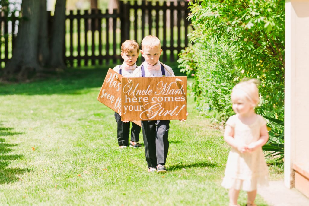 ring bearer holding cute custom handmade sign here comes the bride