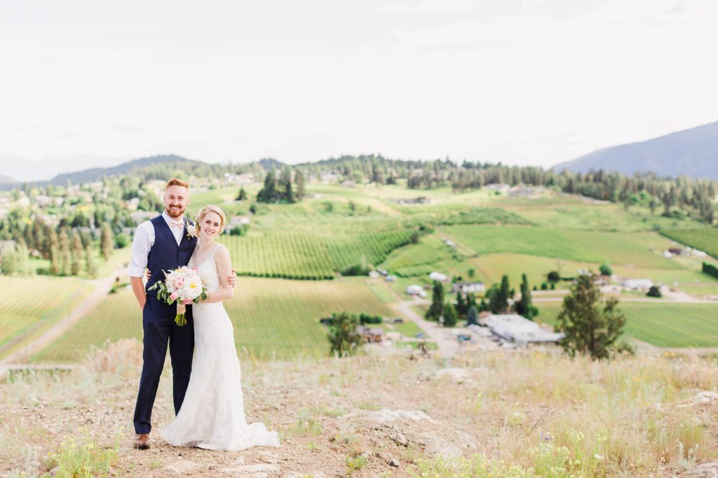 bride and groom smiling on top of a hill surouded by vinyards and mountains