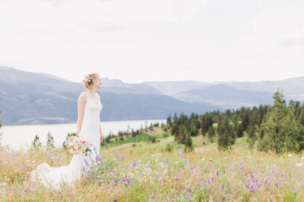 bridal shot as she holds her bouquet on a mountain surrounded by wildflowers