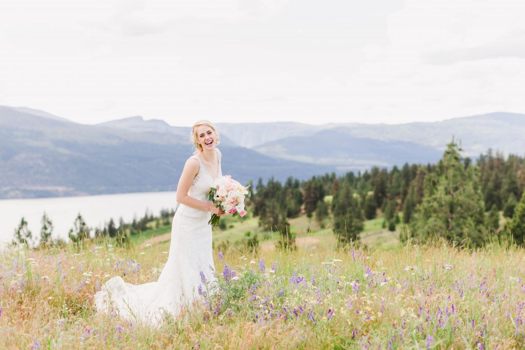 happy bride smiling with her bouquet in kelowna
