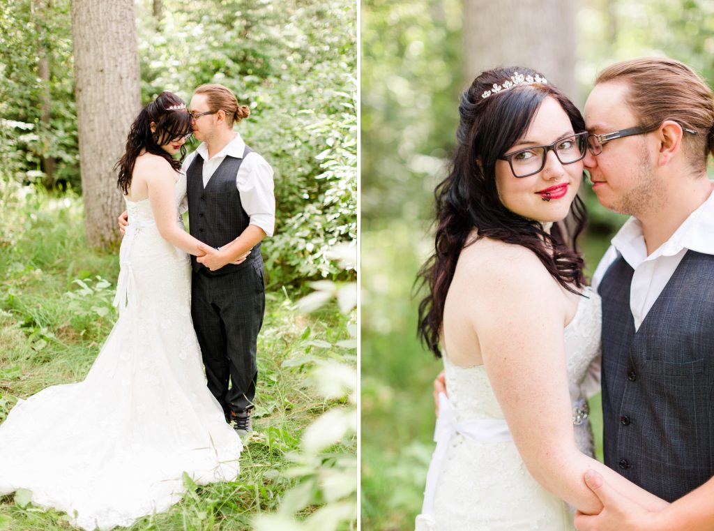 bride and groom holding hands forehead touching in the forest