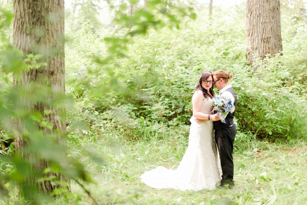 bride and groom hugging in the trees holding her wedding bouquet