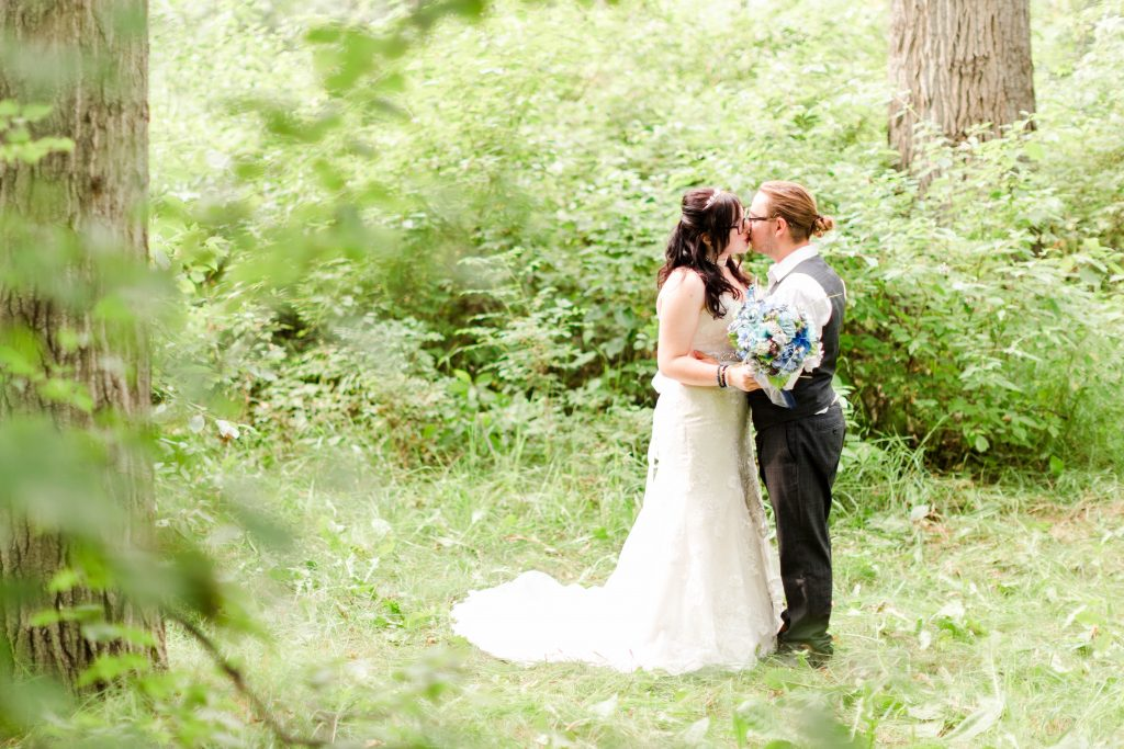 Bride and groom kissing each other in the grande prairie forest and leaves