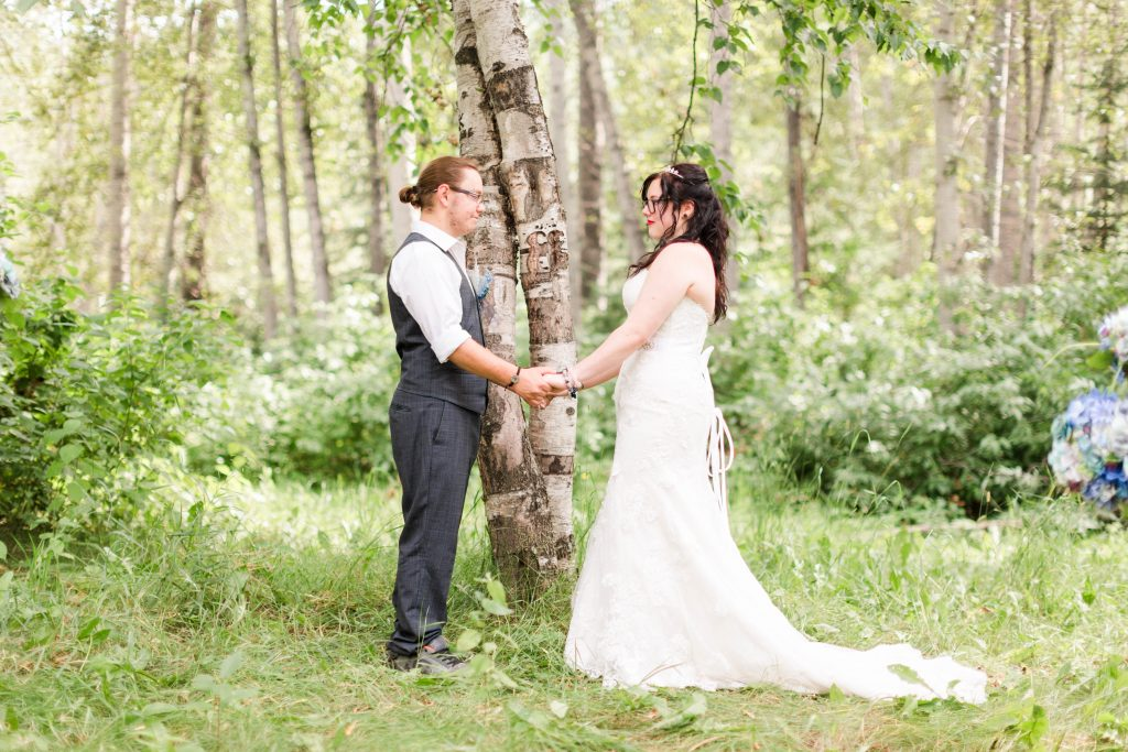 Shelby and corbin bride and groom holding hands during wedding ceremony in front of two intertwined trees