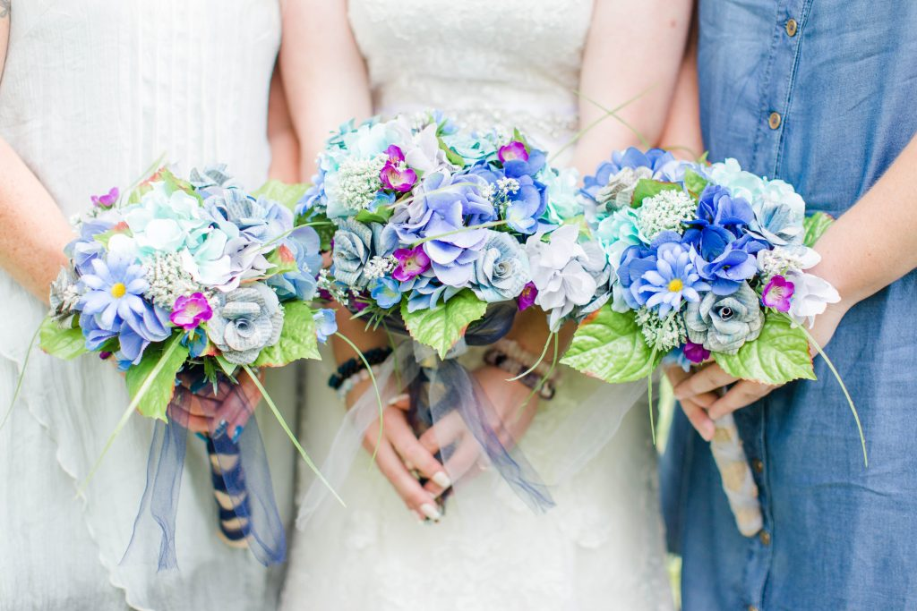 bridemaids and bride holding blue and purple wedding bouquets