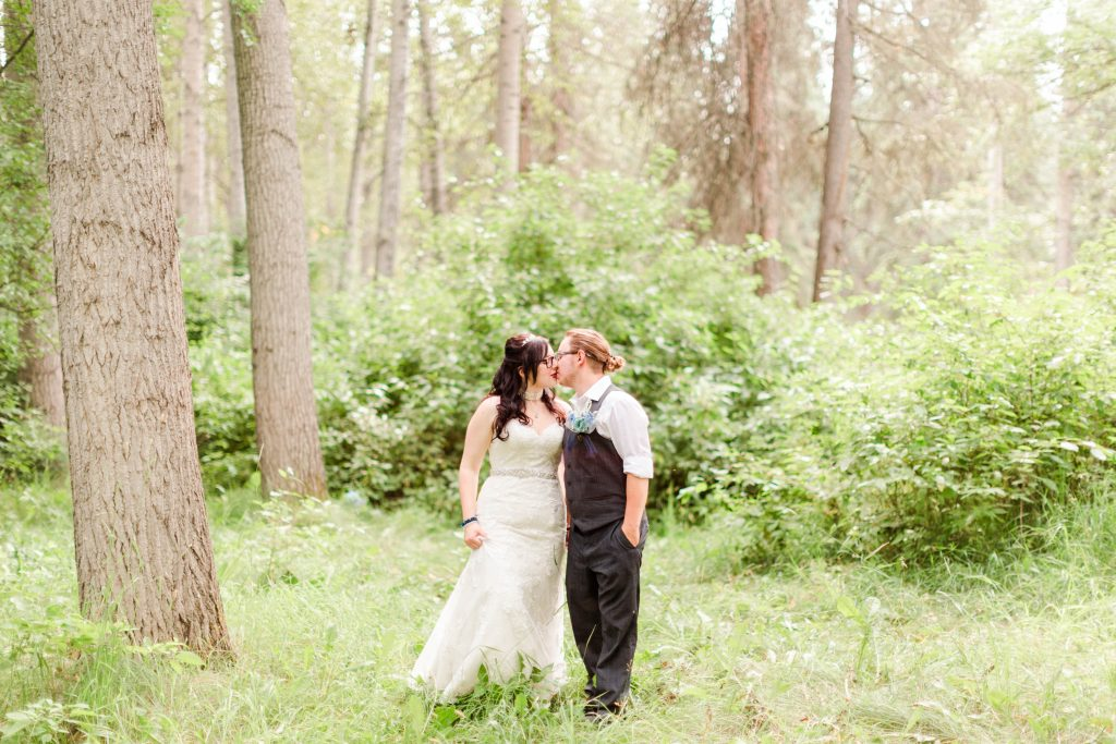 bride and groom kissing each other in grande prairie forest
