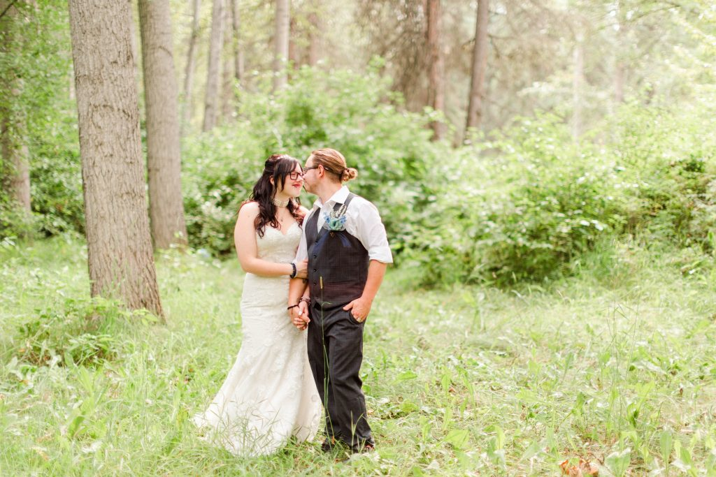 bride and groom smiling at each other in the forest