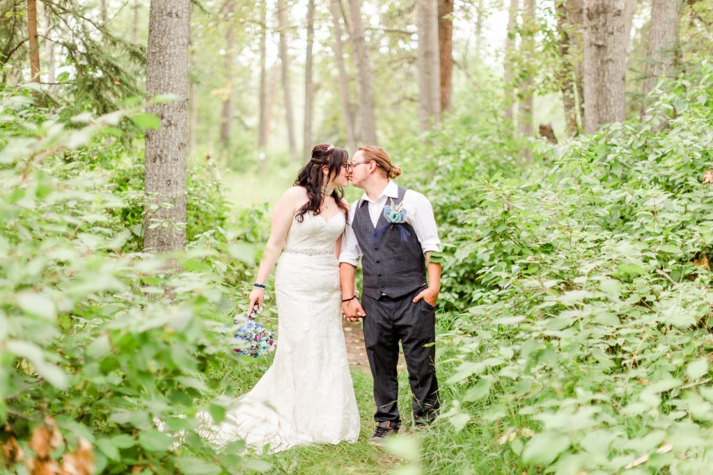bride and groom kissing in the trees and leaves and nature