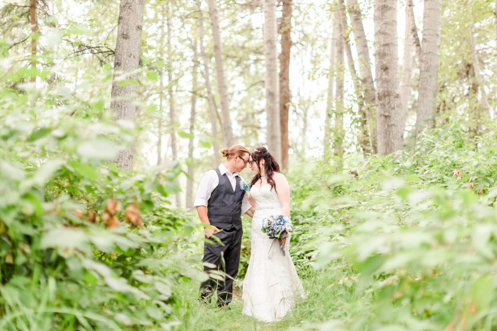 bride and groom in their wedding clothes outside surrounded by beautiful trees