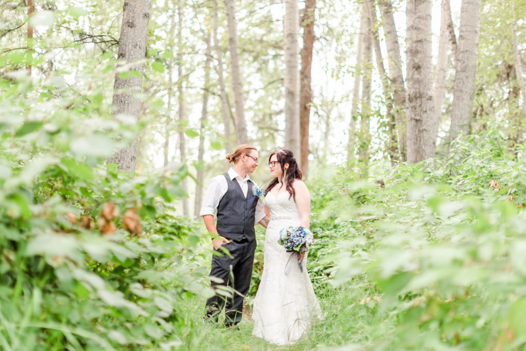 bride and groom looking at each other in the forest
