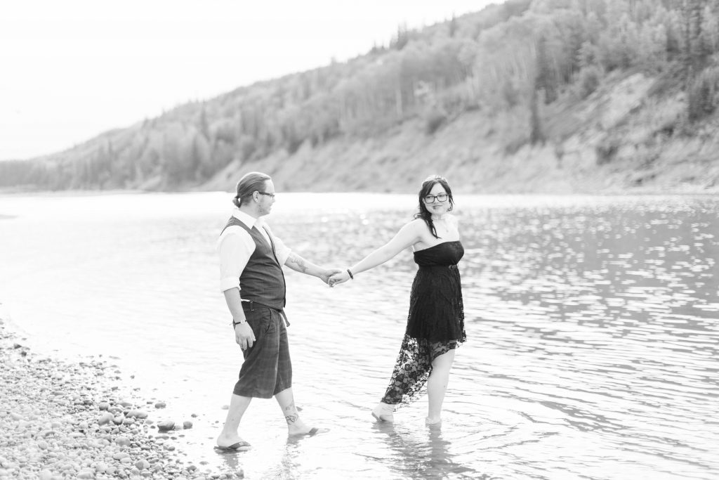 couple walking in the river holding hands. Bride is wearing her dress and smiling.