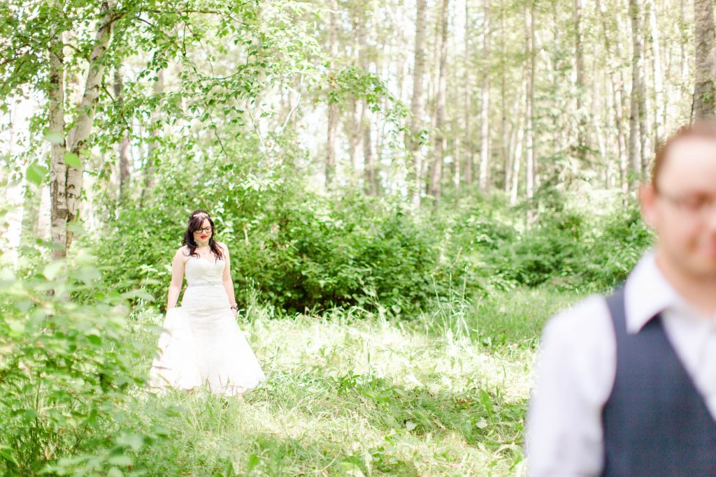 bride walking up to her groom fiance during first look i the outdoor forest