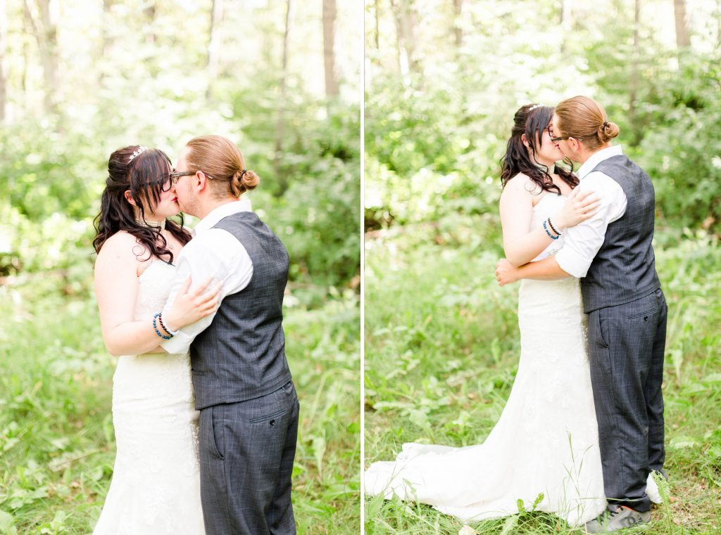 couple kissing each other during first look outside in the forest