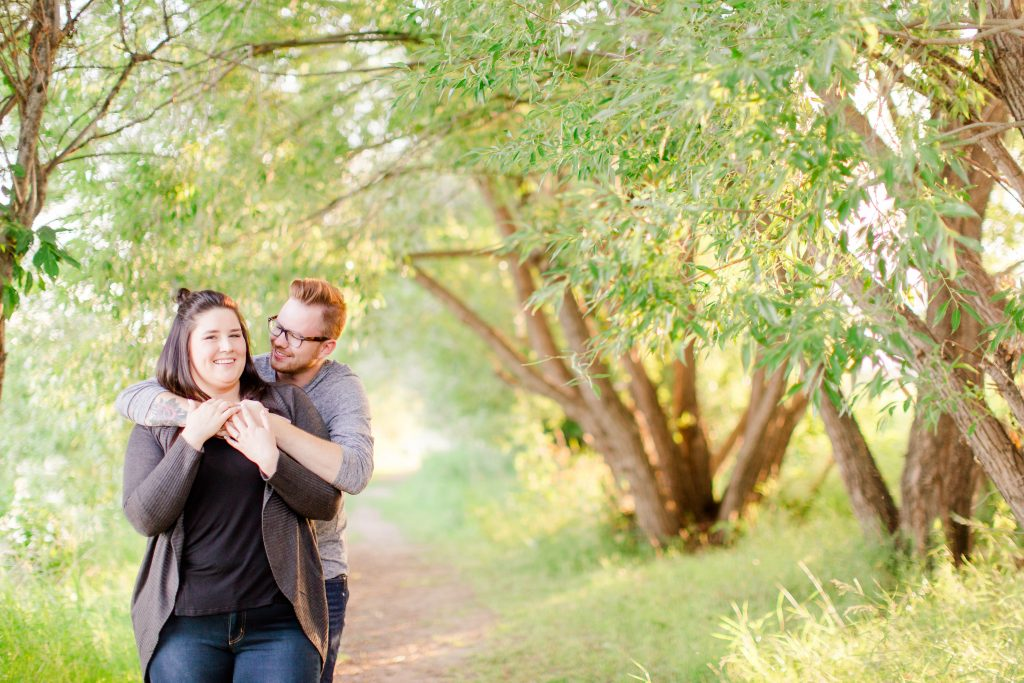 grande prairie engagement couple in a forest path of trees near sunset with kayla lynn photography