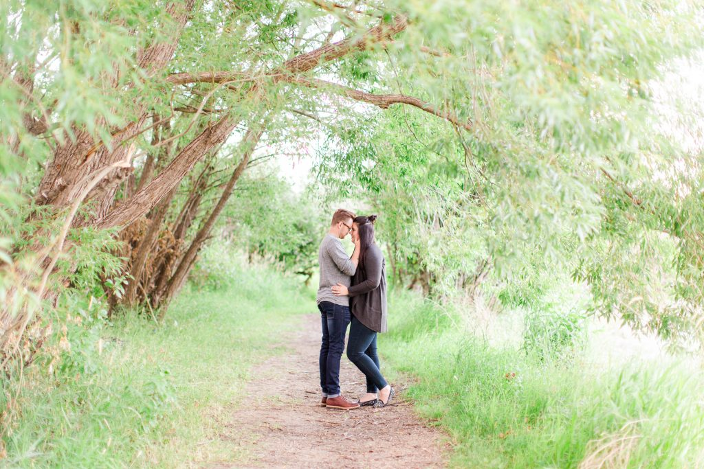 couple facing each other between a beuatiful romantic path of trees. Looks magical