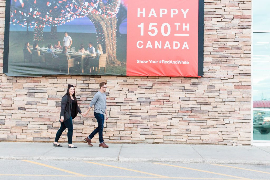 engaged couple robyn and colby walking in front of canadian tire in grande prairie