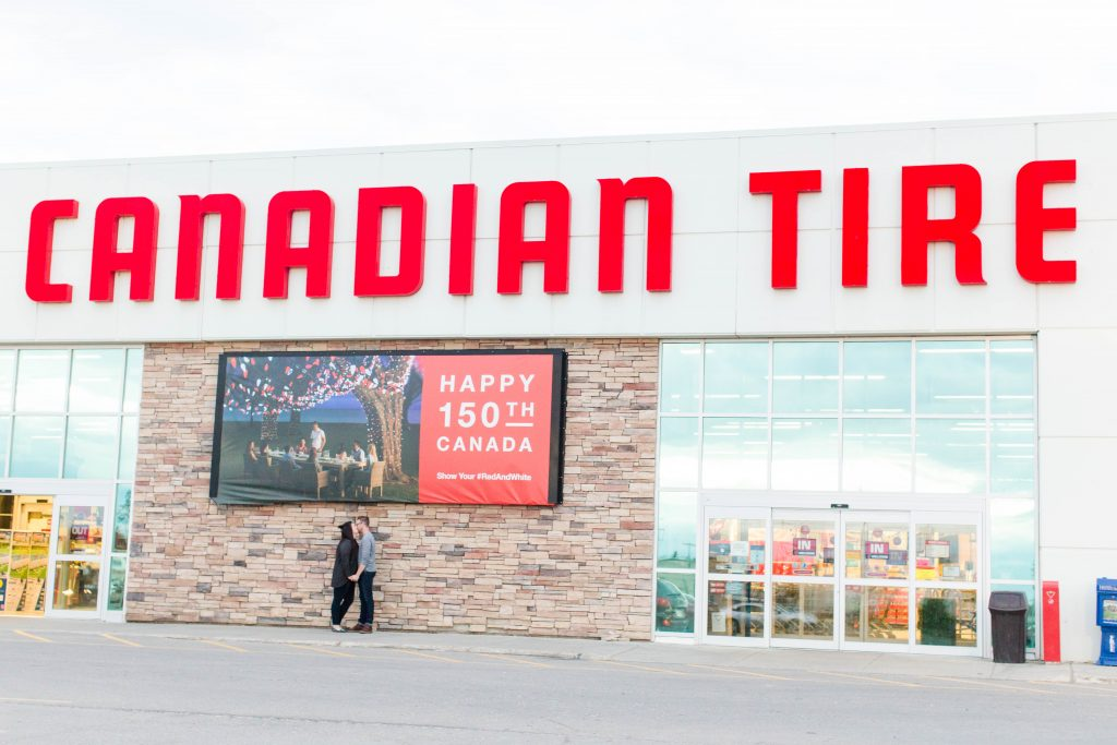 couple engaged couple robyn and colby kissing in front of canadian tire sign in grande prairie alberta