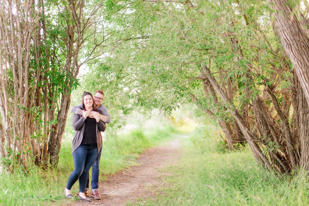couple smilign for the camera on a path of full grown trees green