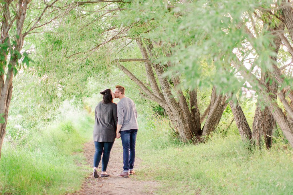 engagement couple kissing each other as they walk along a path