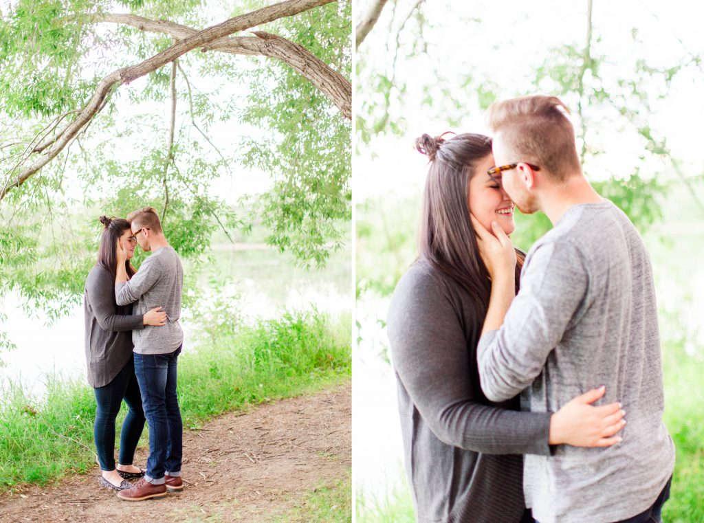 guy going in for kiss during engagement photos near green trees
