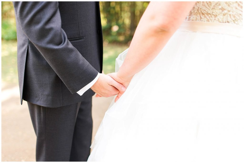bride and groom holding hands during first look