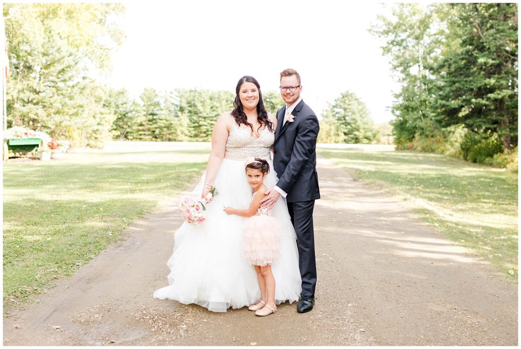 bride and groom with their flower girl niece after the first look