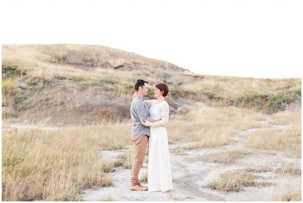 wide landscape photo of husband and wife looks like a wedding as she wears her lace white dress in grande prairie with photographer
