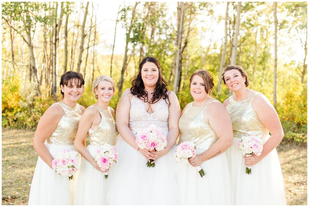bride and her bridesmaids smiling holing blush pink wedding flowers