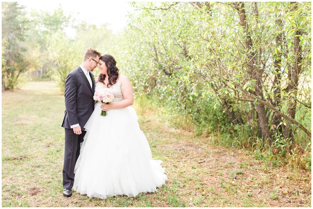 bride and groom forehead touching romantic photo outside beside the trees with kayla lynn photography