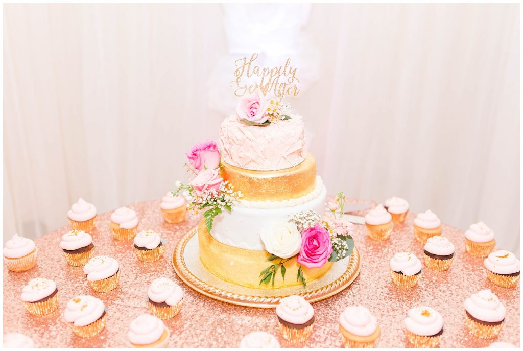 gorgeous blush pink and gold wedding cake with little cupcakes surrounding it wedding photography