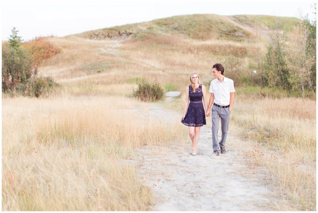 couple walking and holding hands, smiling at each other at Kleskun hills grande prairie