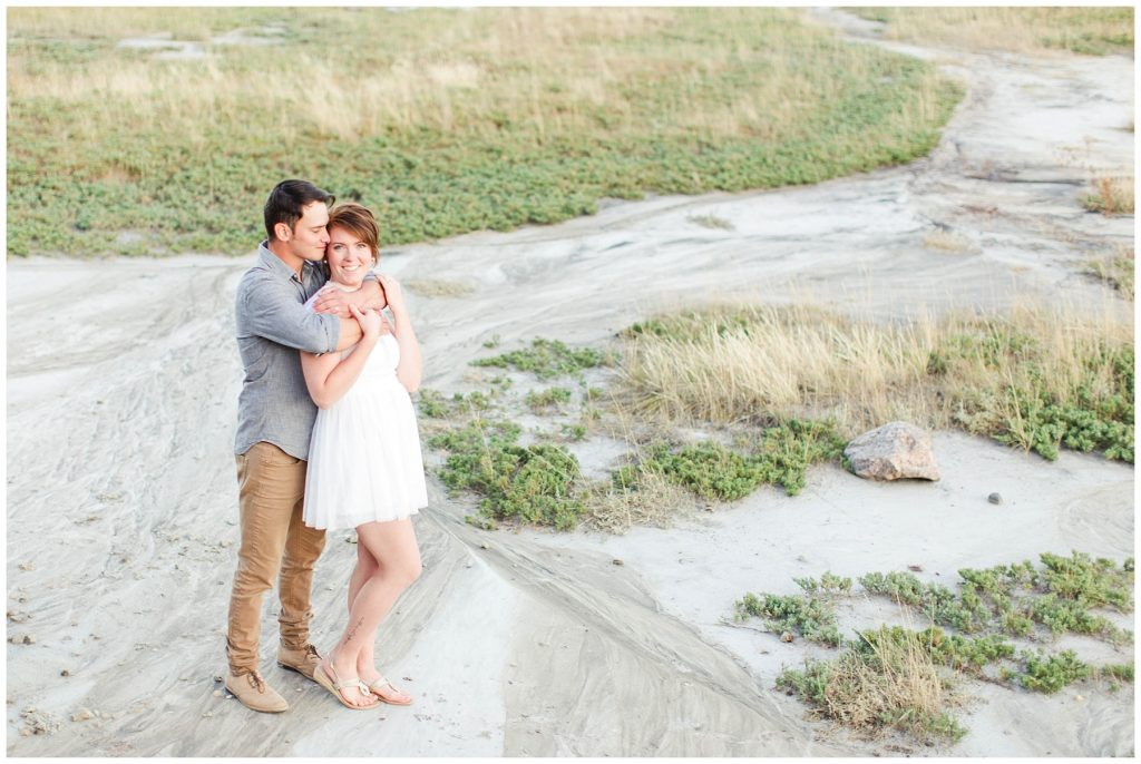 cute couple cuddling in a kleskun hills grande prairie desert with cool sandy ground and green nature