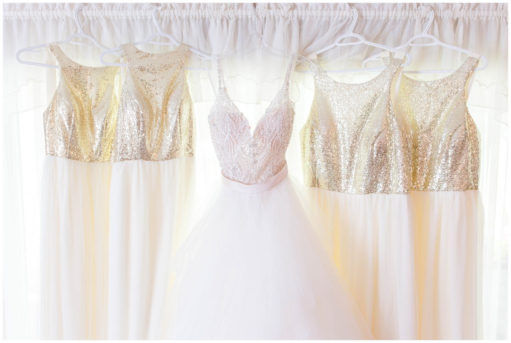 brides and bridesmaids gold and white dresses hanging