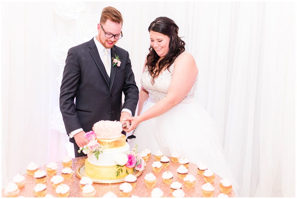 bride and groom cutting their wedding cake at the rec-plex blush pink and gold
