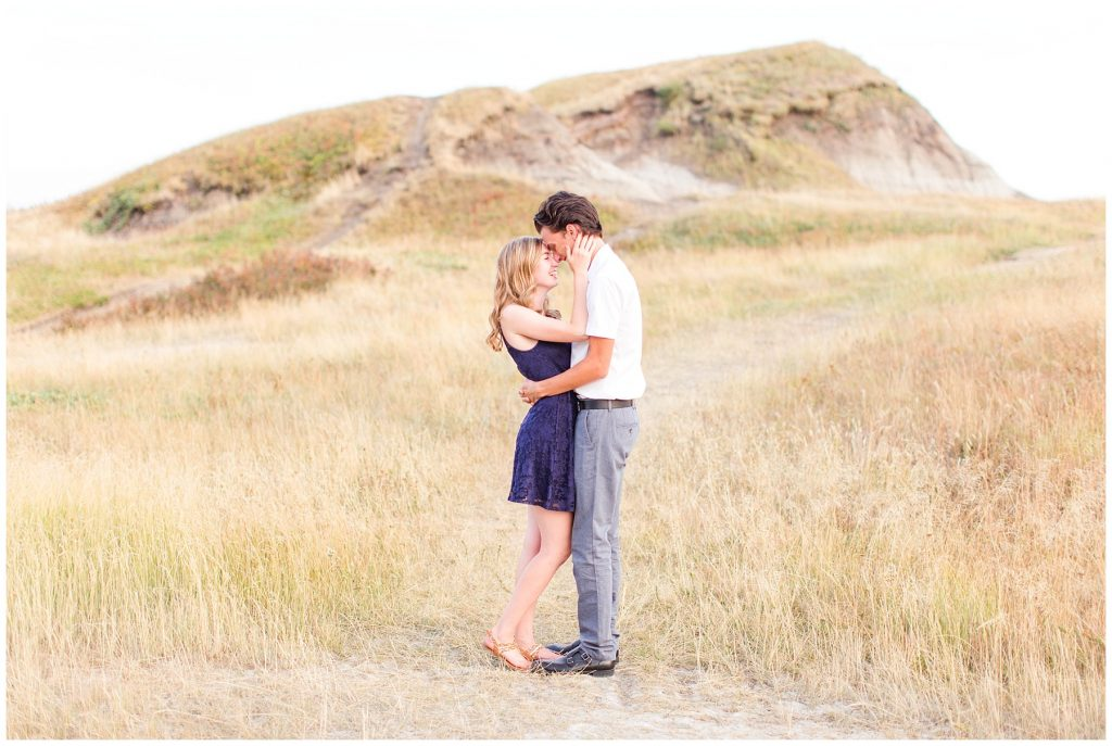 girlfriend and boyfriend chest to chest in front of a hill with light golden grass surrounding them. Their forheads are touching each other and girl girl is wearing navy blue dress at Kleskun hills grande prairie
