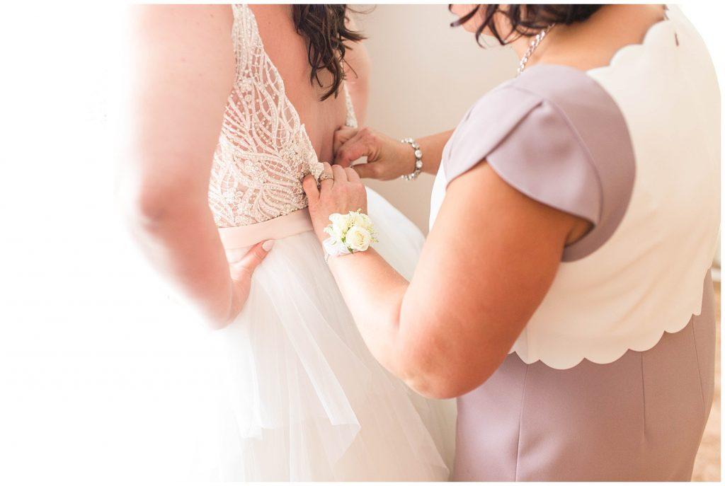 brides mom putting on wedding dress