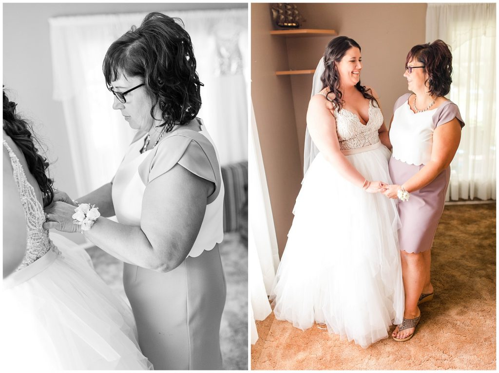 bride's mom putting on brides wedding dress they are also holding hands and smiling at each other