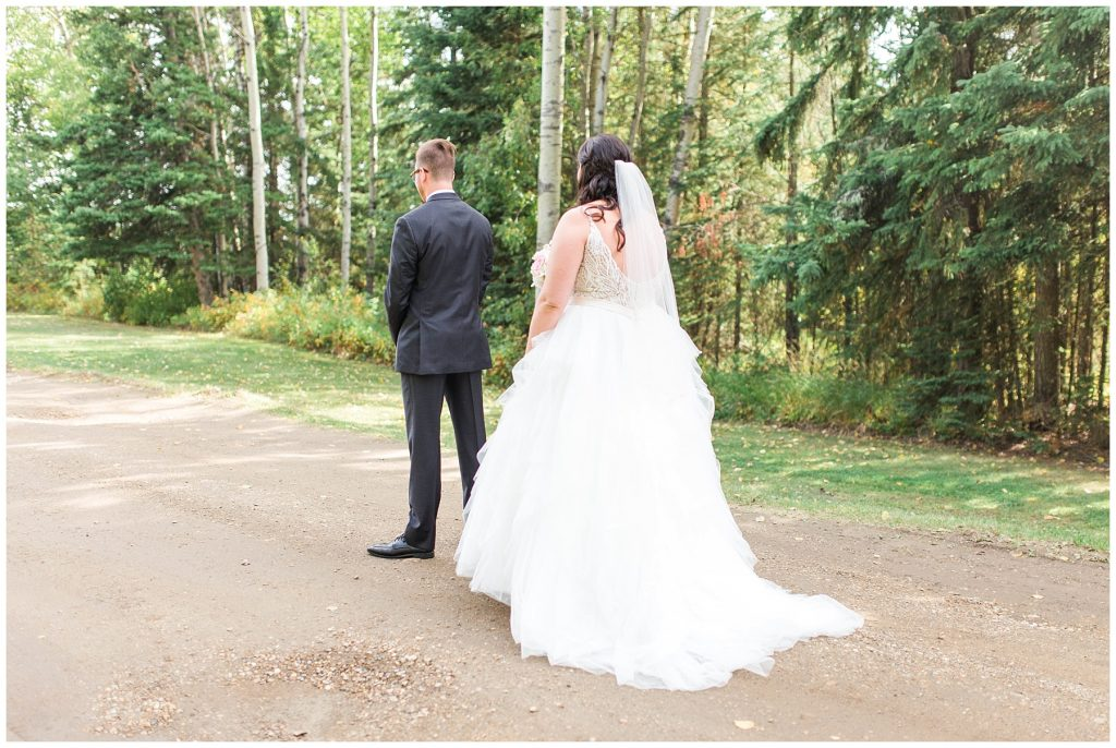 bride walking towards her groom during their first look