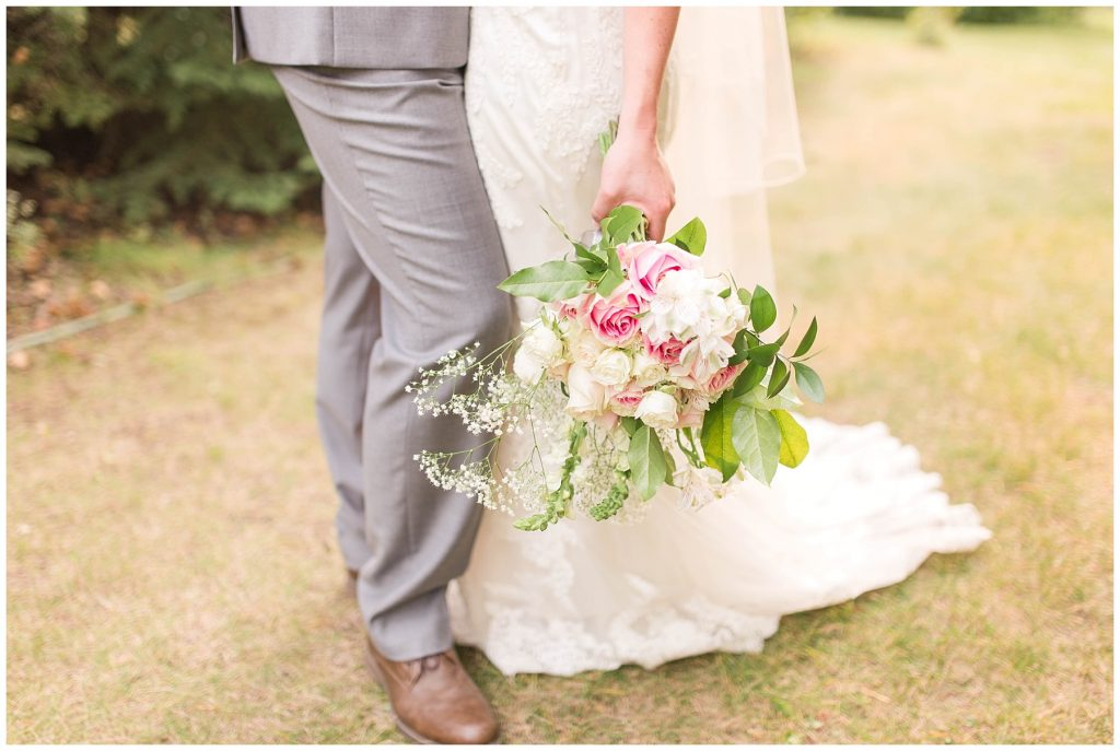 bride and groom holding pink wedding flowers as they stand up close up photo