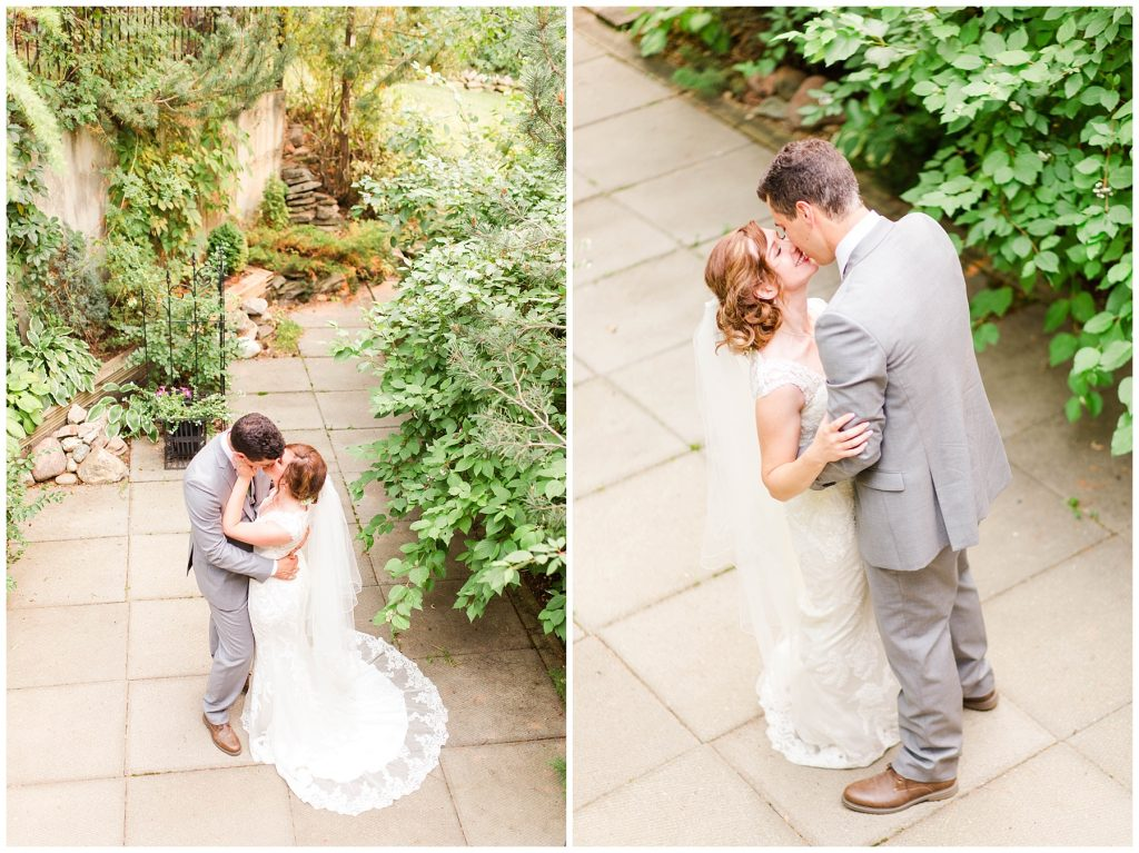 wedding couple kissing surrounded by green leaves and vines