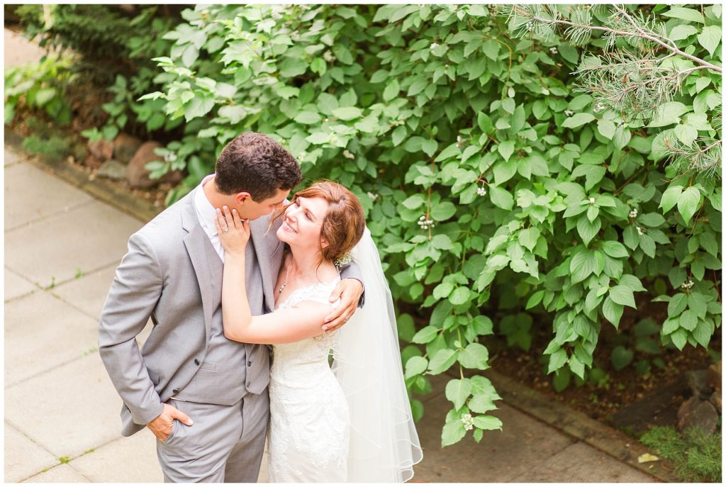 wedding couple smiling in grande prairie photography close up with vines and leaves in the background and smiles