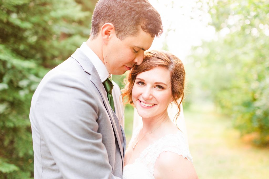 couple close up with beautiful sunshine glow as the bride smiles outside surrounded by yellows and greens