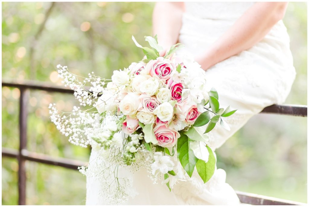 close up shot as bride sits on fence beautiful white and pink flowers