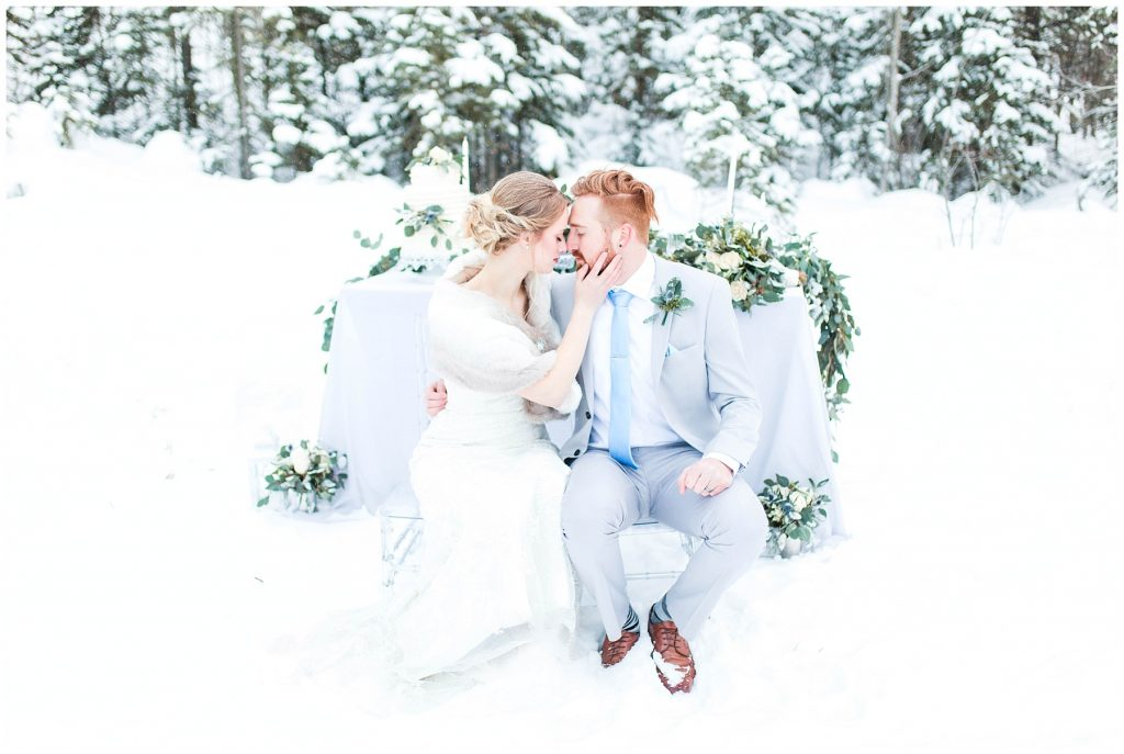 bride and groom sitting on chairs changing dreams to reality nose to nose so romantic groom is wearing a light grey suit wedding photographer grande prairie by kayla lynn photography