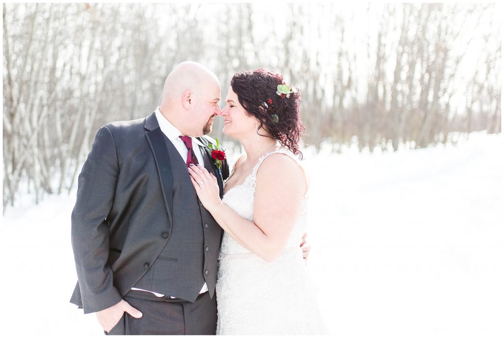 cute couple in the winter nose to nose and a close up on their wedding day outside with light shinning behind them